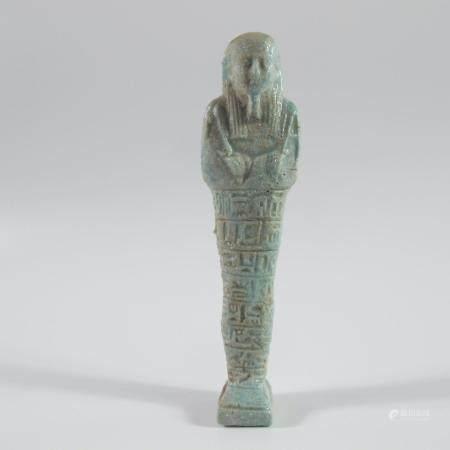 EGYPTE. OUSHEBTI INSCRIT PORTANT LES INSTRUMENTS ARATOIRES. Faïence bleue. L. env. 9 cm. Style