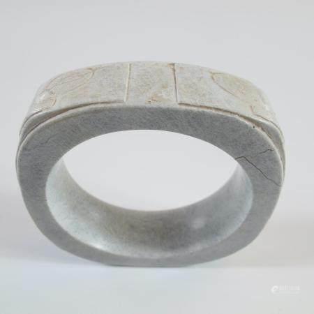 CHINE. BRACELET RITUEL CONG ORNE DE QUATRE MASQUES CHAMANIQUES. Jade calcifié. L 8.5 cm. Veines