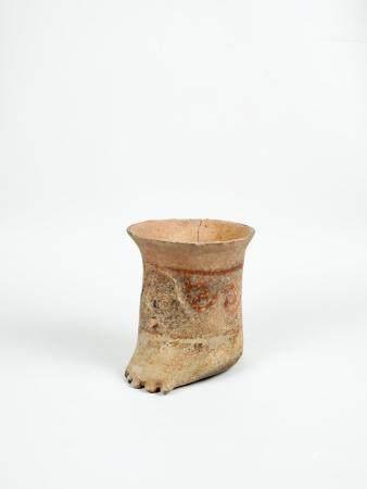 Curieux vase en forme de pied à décor de personnages en relief et d'un décor géométrique Terre
