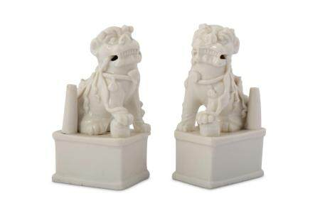 A PAIR OF CHINESE BLANC-DE-CHINE LION DOG JOSS STICK HOLDERS