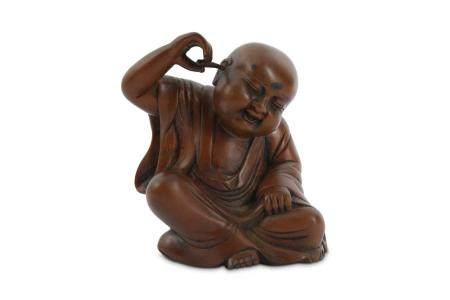 A CHINESE WOOD CARVING OF A BOY CLEANING HIS EAR.
