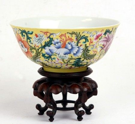 A Chinese famille rose bowl decorated with flowers on a yellow ground, blue seal mark to the