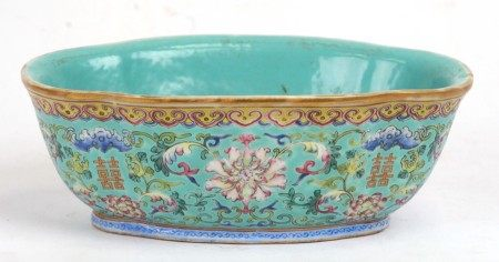 A Chinese famille rose shaped oval bowl decorated with flowers and characters on a turquoise ground,