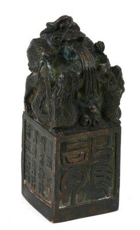 A Chinese bronze seal, the top with a mythical beast, on a square platform with character marks,