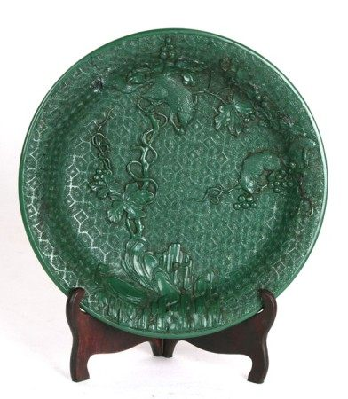 A Chinese green cinnabar lacquered dish decorated with squirrels amongst fruit trees, 24cms (9.5ins)