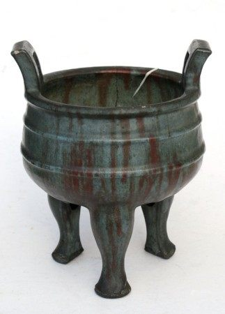 A Chinese two-handled pottery censer on three legs, multi-character seal mark to the underside,