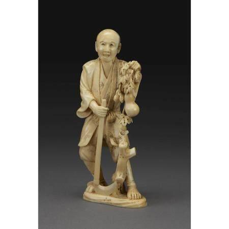 ~ OKIMONO  en ivoire, représentant un homme tenant une branche de colo