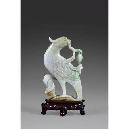 STATUETTE D'OISEAU  en jade jadéite, représenté debout, tenant dans so