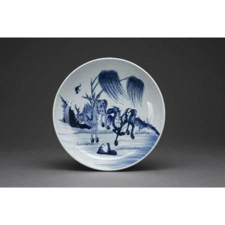 PLAT CREUX   en porcelaine et émaux bleu sous couverte, à décor de deu