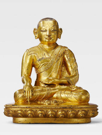 A GILT COPPER ALLOY FIGURE OF THE SIXTH ABBOT OF DRIGUNG MONASTERY, TOKKHAWA RINCHEN SENGGE CENTRAL TIBET, DENSATIL, 14TH CENTURY