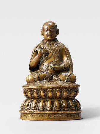 A SILVER AND COPPER INLAID BRASS FIGURE OF LOWO KHENCHEN SONAM LHUNDRUP, ABBOT OF THE KINGDOM OF LO  TIBET, 16TH CENTURY