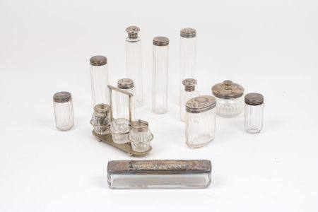 A collection of silver topped glass vanity jars, comprising a set of five jars of various shape with