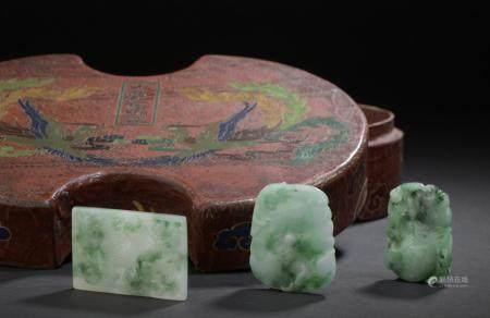 Trois pendentifs en jadéite et leur boîte en bois laquéChineLes pendentifs à décor de fleurs, d