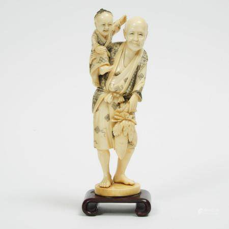 A Ivory Okimono of an Old Man with Child, height 9.2 in — 23.4 cm