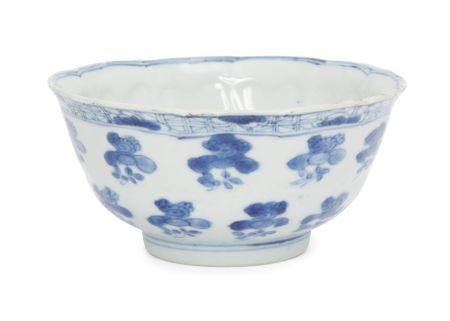 A Chinese porcelain moulded bowl, Kangxi period, painted in underglaze blue with floral sprays to