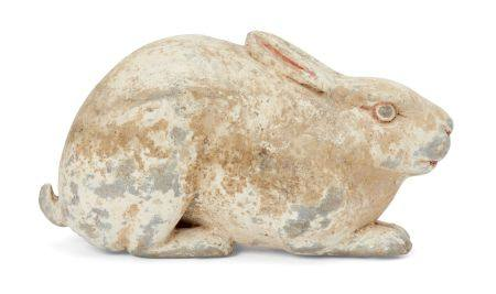 A Chinese grey pottery hare, Han dynasty, modelled crouching facing forwards in alert pose with long