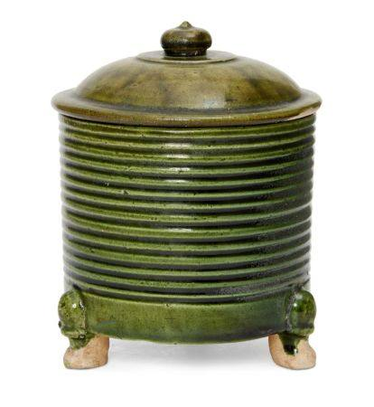 A rare Chinese green-glazed pottery tripod jar and cover, Tang dynasty, the cylindrical ribbed