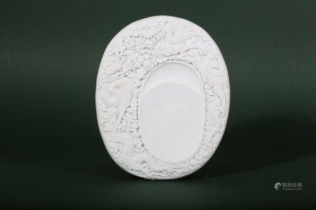 A CHINESE WHITE BISCUIT 'DRAGON' INKSTONE.