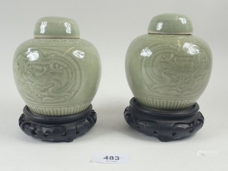 A pair of Chinese Celadon ginger jars with incised decoration, 11cm tall, on stands