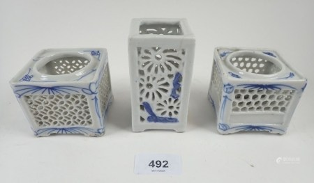 Three Chinese pierced blue and white porcelain candle holders