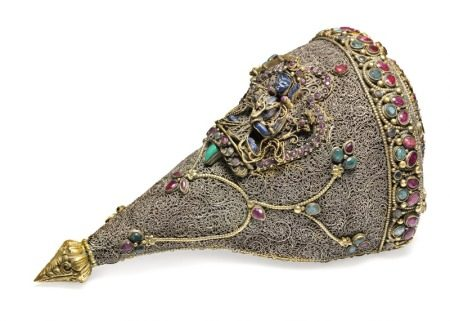 A Buddhist ritual conch horn mounted with filigree all over and bands set with rubies and emeralds, on the front a lapis lazuli figure of Manjushri. 19th-20th century. L. 19 cm.