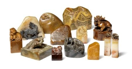 A collection of 12 Chinese soapstones and one wooden seal carved with Foo-dogs, lions, dragons, rams, toad and landscapes, seal faces with signatures or poetry. Qing and Republic period. H. 3–7 cm. (13)       Provenance: Danish private collection based on two generations' stay in China 1885–1945.