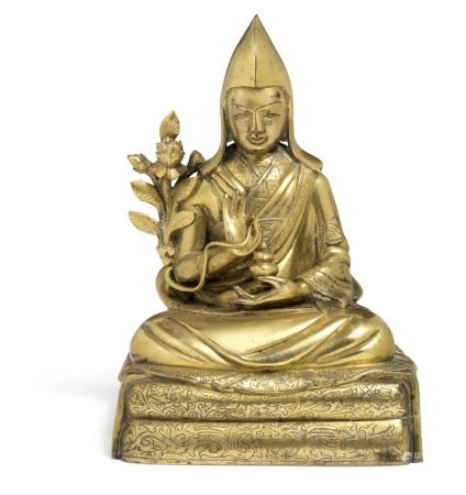 A Tibetan gilt bronze figure of lama Tsongkhapa seated in dhyanasana on a double cushion throne covered by two blankets, engraved with flowers and foliage. Right hand in vitarka mudra, the left resting on his lap carrying a lidded jar. His right side flanked by a lotus stem. Sealed bottom, circa 1800. Weight 1087 g. H. 15 cm.        Provenance: From a Danish private collection.