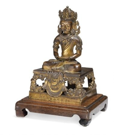 "A gilt bronze Amitayus Buddha, seated on a squared throne with cascade cloth falling at the front. The hands holding a now missing kalash. The face with downcast eyes below the high crown with floral ornament. Wearing long flowing robes, earrings and a necklace. Throne bearing inscription on the front ""made in the Qianlong period"". Tibet-China 1736–1795. Weight 763 g. H. 18.5 cm. Wooden base incl.       Provenance: Danish private collection."
