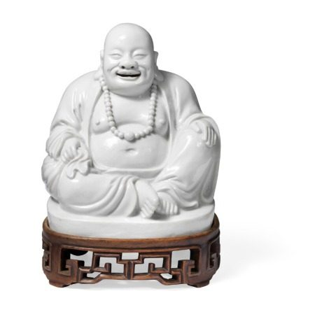 A Chinese Dehua ware laughing Budai seated and holding a sack. Kangxi 1662–1722. H. 19.5 cm. Fitted carved wood stand enclosed. H. 5.5 cm.        Provenance: Danish private collection.