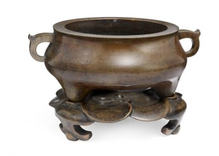 A Chinese patinated bronze tripod censer with two handles. Xuande seal mark. And matching bronze stand cast as petals, supported by three low feet. 17th-18th century. Censer weight 1279 g. H. 6 cm Diam. 13 cm. Base weight 707 g. (2)       Provenance: Danish private collection based on two generations' stay in China 1885–1945.