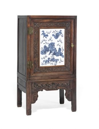 A Chinese hongmu cupboard on stand carved in relief, the front door inlaid with large porcelain panel decorated in blue with playing dogs. Guangxu 1875–1908, late 19th century. H. 137 cm. W. 74 cm. D. 51 cm.       Provenance: The late antique dealer Steen Strømberg, b. 1947- d. 2014.