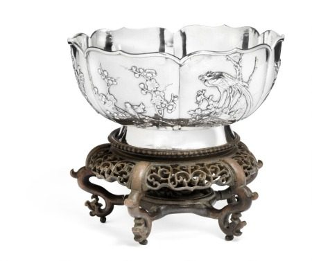 A Chinese silver bowl with applied decoration of flowering prunus, magnolia, calabash fruits, chrysanthemums and birds. Maker's mark presumably Wing Chun, Hong Kong. 19th-20th century. Weight 649 g. Diam. 20.5 cm. H. 10 cm. Carved wood stand incl.       Provenance: Engineer Rasmus Black 1871–1937, Sophus Black's elder brother, was employed by Northern Telegraph Company and stationed in China 1898–1917.