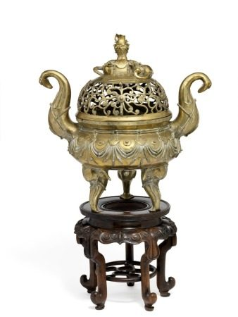 "A Chinese bronze ""elephant"" censer and cover, bombé-shaped body cast with harness in relief. Handles in shape of raised elephant trunks; supported on three harnessed elephant heads. Pierced cover with foliage, finial forming a caparisoned recumbent elephant carrying a vase. Mark of Tian He Liu Nian Du Zhi. Qing, 19th century. Weight 12303 g. H. 51 cm. Carved wooden stand incl. H. 29 cm.       Provenance: Danish private collection."