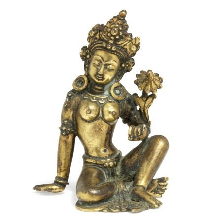 A Nepali gilt bronze figure of a female bodhisattva, wearing a dhoti, crown, arm rings and large earrings, she is seated in rajalilasana, the left hand holds the stem of a lotus flower flanking her shoulder. 18th century. Weight 234 g. H. 7.5 cm.        Provenance: Ph.D. and M.Sc.Eng. Jesper Trier 1932–2017 and wife.