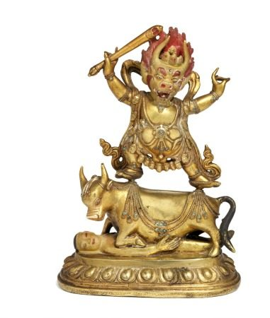 A Tibetan gilt and painted bronze figure of a striding ithyphallic Yama Dharmaraja, with three-eyed buffalo head and flaming red hair, right hand holds a stick with a skull, adorned with a crown of skulls and necklace with severed heads. He stands on a kneeling buffalo and human figure. Sealed bottom. 18th century. Weight 1131 g. H. 17.5 cm.         Provenance: Nurse anesthetist Birgit Trier and Ph.D. and M.Sc.Eng. Jesper Trier 1932–2017.