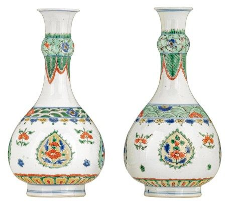 A pair of famille verte bottle vases, the leaf-shaped cartouches decorated with