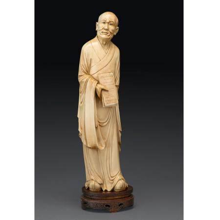 """~GRAND SUJETen ivoire, représentant un lettré en pied, tenant un livre inscrit """"Confucius a dit"""