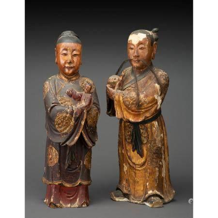 COUPLE DE DIGNITAIRESen bois laqué et doré, la femme en vêtement traditionel, sa robe ornée de