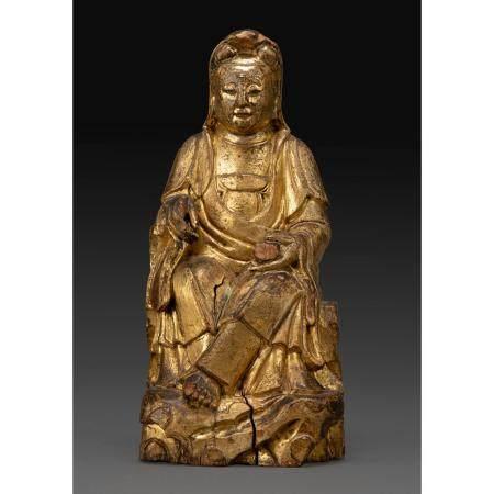 STATUETTEen bois laqué et doré, représentant la déesse Guanyin assise sur un rocher et tenant u