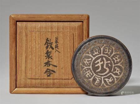 Un kôgo de fer. 29e siècle  Sur le couvercle plat, un bonji central entouré de huit autres bonj