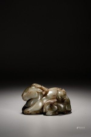 A CHINESE CELADON JADE CARVED SEATED RAM