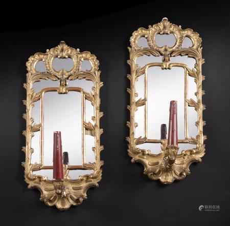 Paire de miroirs porte-lumière en bois argenté, à décor de chimères, feuillages [...]