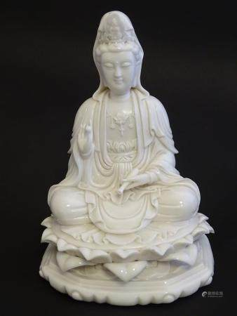 """A Chinese blanc de chine figure depicting Guanyin seated on a lotus flower base. Approx. 7 1/2"""" high"""