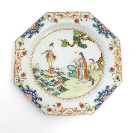 A Chinese plate of octagonal form decorated in famille rose depicting figures in a coastal landscape