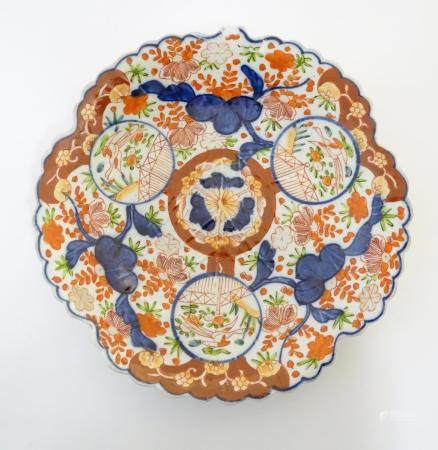 A Japanese Imari plate with a scalloped rim with stylised leaf veins in relief to the centre,