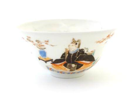 A Japanese small bowl depicting seated figures, a male figure in robes to one side, and a female