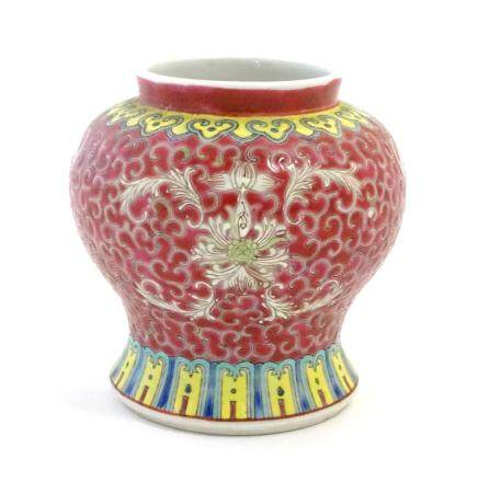 A Chinese famille rose squat vase with a flared base, the body with floral motifs and stylised bat