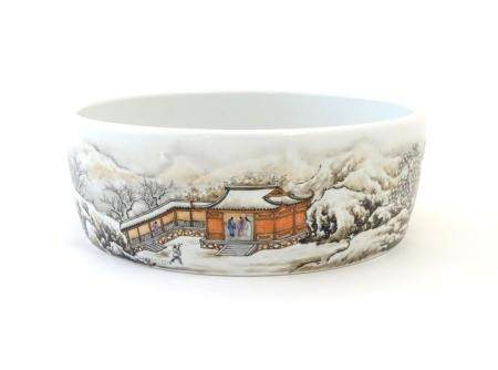 A Chinese circular dish with hand painted decoration depicting a winter snowy landscape scene with