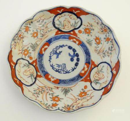 An Imari style plate with a lobed rim, decorated with floral and foliate scenes with panelled