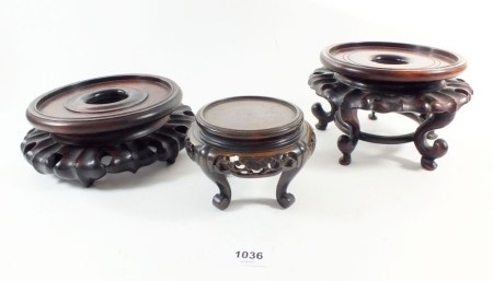 Three carved Chinese hardwood stands, the largest 19cm diameter